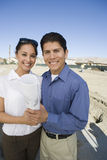 Couple With Blueprint At Under Construction Plot Royalty Free Stock Photography
