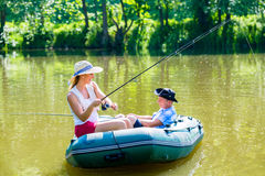 Couple in boat on pond or lake fishing. Women with angle and men is steering stock photo