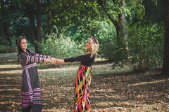 Couple of boho style women play or  dance in  park summer day Stock Images