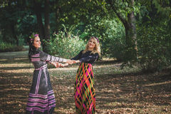 Couple of boho style women play or  dance in  park summer day Royalty Free Stock Image