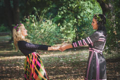 Couple of boho style women play or  dance in  park summer day Royalty Free Stock Photos
