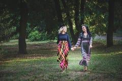 Couple of boho style women run barefoot through the park Stock Photo