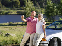 Couple on bonnet of car taking photograph of themselves by river Royalty Free Stock Photography