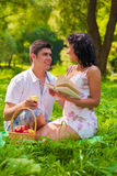 Couple with book and apple in park Royalty Free Stock Images