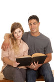 Couple with a book both looking with smiles Royalty Free Stock Photos