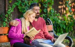 Couple with book and laptop search information. Share or exchange information knowledge. Man and woman use different. Couple with book and laptop search stock image