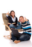 Couple, book laptop sofa stock images