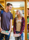 Couple with books looking at each other in the library Stock Photography