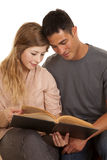 Couple both looking at a book while sitting Stock Photos