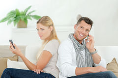 Couple both using their phones on sofa Stock Photography
