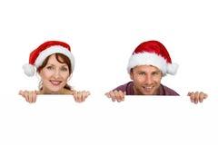 Couple both wearing santa hats Stock Image