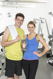 Couple With Bottle Of Water And Towel At Health Club Royalty Free Stock Photography