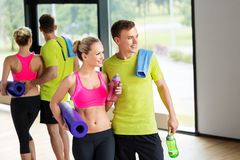 Couple with bottles, exercise mat and towel in gym. Sport, fitness and people concept - smiling couple with water bottles, exercise mat and towel in gym stock photo