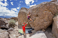 Couple Bouldering. A couple bouldering at the Happy Boulders with the women climbing and the men spotting Royalty Free Stock Photo