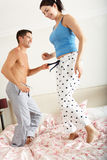 Couple Bouncing On Bed Together Stock Photo