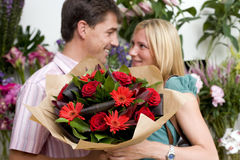 Couple with bouquet of flowers in shop, smiling at each other Stock Photo
