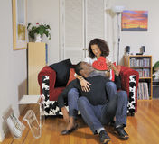 Couple with a box of chocolates. Man sitting on the floor as part of a mixed-race couple handing up a box of chocolates to his seated wife Royalty Free Stock Photography