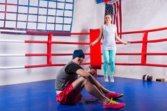 Couple of boxers exercising with jumping rope. In a regular boxing ring surrounded by ropes in a gym Stock Photography