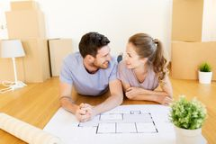 Couple with boxes and blueprint moving to new home Royalty Free Stock Photos