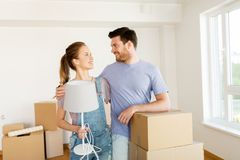 Couple with boxes and lamp moving to new home Stock Photo