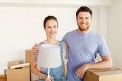 Couple with boxes and lamp moving to new home Royalty Free Stock Photos