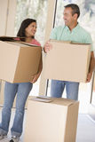 Couple with boxes moving into new home. Smiling Stock Photos