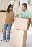 Couple with boxes moving into new home Royalty Free Stock Images
