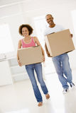 Couple with boxes moving into new home smiling Royalty Free Stock Images