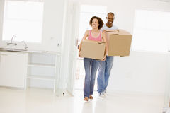 Couple with boxes moving into new home smiling Royalty Free Stock Photos