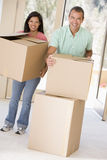 Couple with boxes moving into new home smiling stock photo