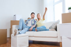 Couple with boxes moving to new home and dreaming. People, repair and real estate concept - smiling couple with boxes moving to new home and dreaming Stock Image