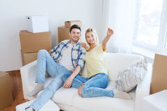 Couple with boxes moving to new home and dreaming. People, repair and real estate concept - smiling couple with boxes moving to new home and dreaming Royalty Free Stock Image