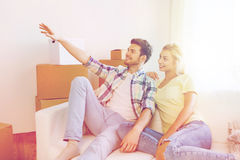 Couple with boxes moving to new home and dreaming. People, repair and real estate concept - smiling couple with boxes moving to new home and dreaming Royalty Free Stock Images