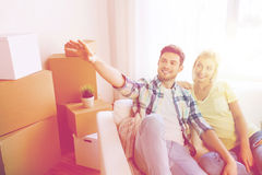 Couple with boxes moving to new home and dreaming. People, repair and real estate concept - smiling couple with boxes moving to new home and dreaming Stock Photography