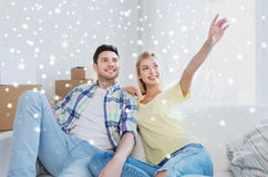Couple with boxes moving to new home and dreaming. People, repair and real estate concept - smiling couple with boxes moving to new home and dreaming over snow Royalty Free Stock Images