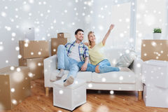 Couple with boxes moving to new home and dreaming. People, repair and real estate concept - smiling couple with boxes moving to new home and dreaming over snow Stock Photo