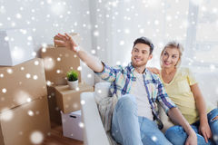 Couple with boxes moving to new home and dreaming. People, repair and real estate concept - smiling couple with boxes moving to new home and dreaming over snow Royalty Free Stock Photo