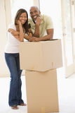 Couple with boxes in new home smiling Stock Photos