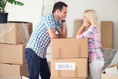 Couple with boxes in new home smiling. Looking at each other royalty free stock images