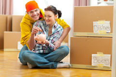 Couple among boxes putting coin in piggy bank. Young couple among boxes putting coin in piggy bank Stock Photos