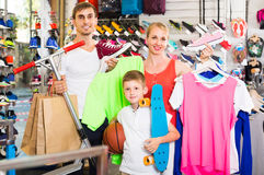 Couple with boy choosing shoes in sport shop Royalty Free Stock Images