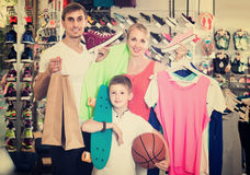 Couple with boy choosing shoes in sport shop Royalty Free Stock Photography