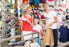 Couple with boy choosing shoes in sport shop Royalty Free Stock Photos