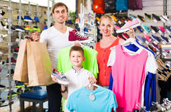 Couple with boy choosing shoes in sport shop Stock Images