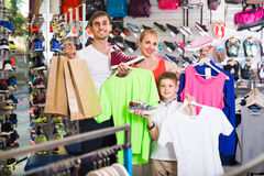 Couple with boy choosing shoes in sport shop Royalty Free Stock Image