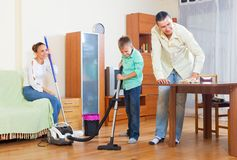 Couple and boy dusting together Royalty Free Stock Image