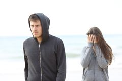 Couple break up on the beach with a man leaving girl. Couple break up on the beach with a men leaving girl alone stock photography