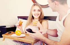 Couple with breakfast in bed stock images