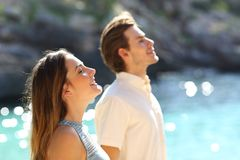 Couple breathing fresh air on the beach on vacation stock photos