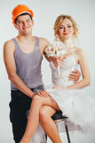 Couple of bride and groom in helmet. Young couple of bride with bunch of flowers in stylish wedding dress and groom in helmet and sleeveless vest Royalty Free Stock Photos